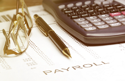 Payroll Services concept, glasses, pen and calculator on some financial documents